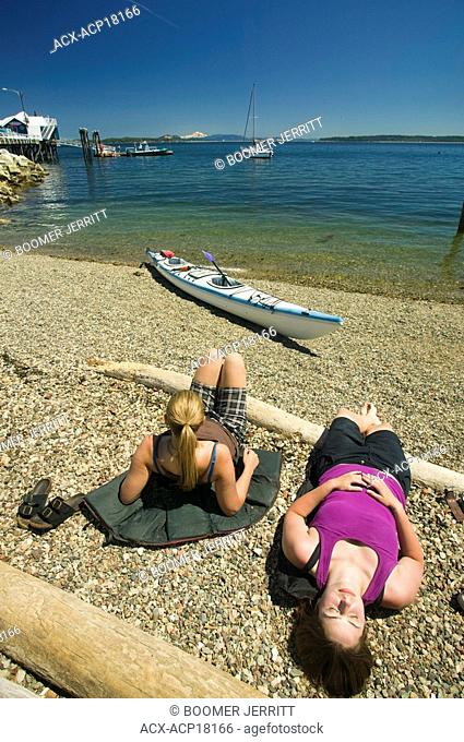 Relaxing on the beach after a paddle near the Sidney Spit, these two kayakers find solace in sun and scenery, Sidney, Southern Vancouver Island