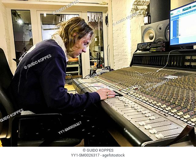 Berlin, Germany. Music student Lucas working on his skills inside a professional music studio