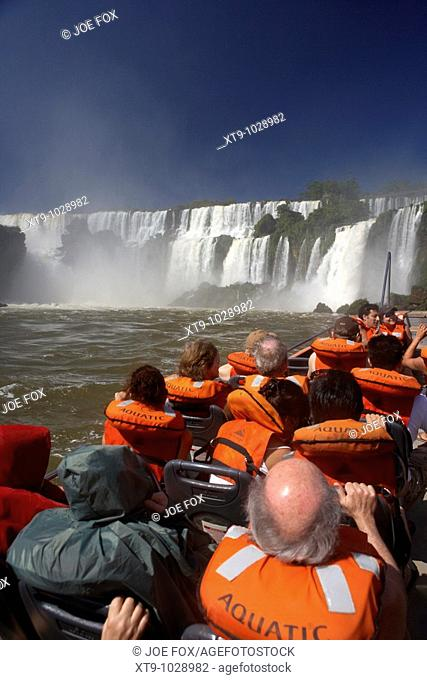 group of tourists on speedboat underneath waterfalls iguazu national park, republic of argentina, south america