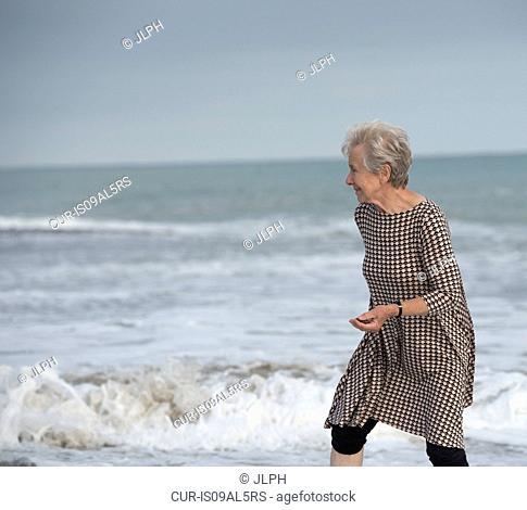 Senior woman running from ocean wave on beach, Dana Point, California, USA
