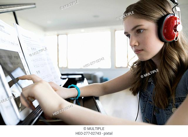 Focused girl with digital tablet headphones at piano