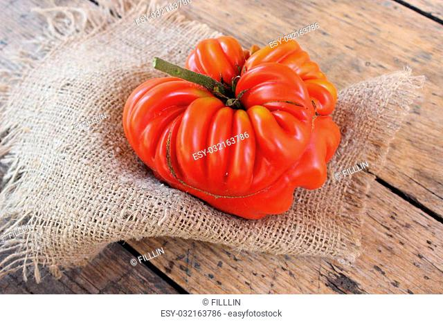 Big red tomato on a linen cloth