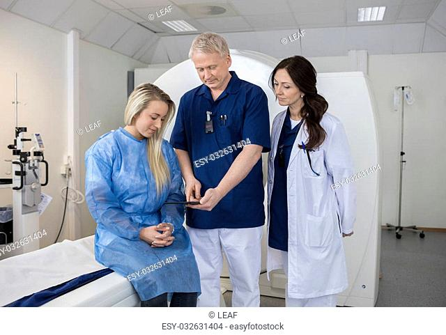 Mature professional with patient and doctor using computer before MRI scan in hospital