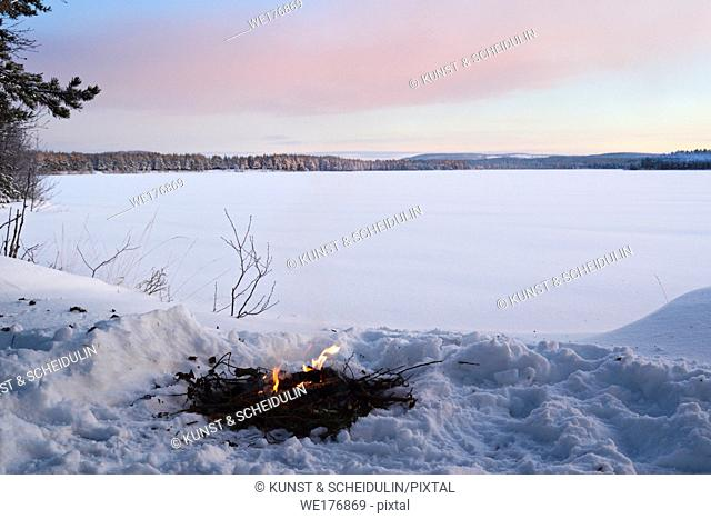 Fire burning in the snow at the shore of a lake at sunset