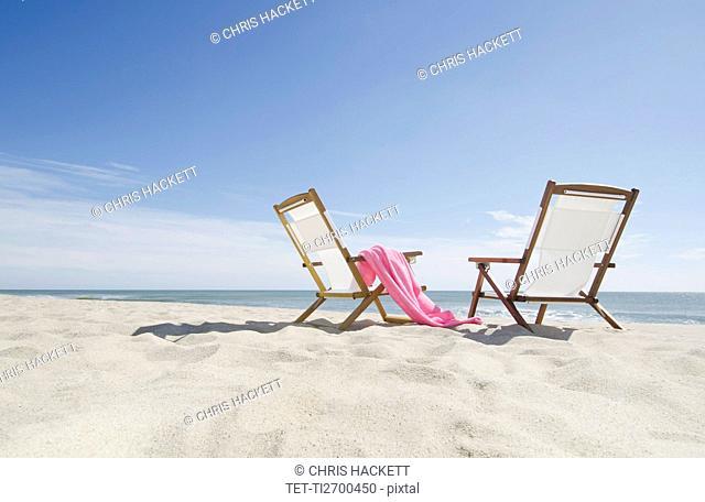 empty lounge chairs on sandy beach