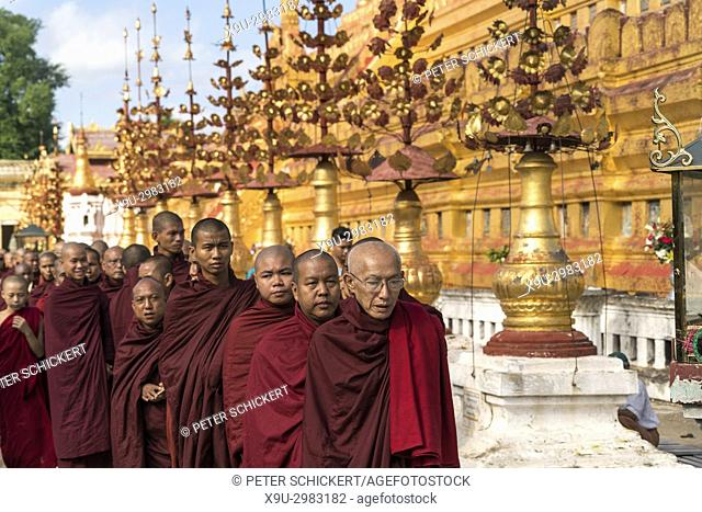 row of monks lining up for alms and donations, Shwezigon Pagoda, Bagan, Myanmar, Asia