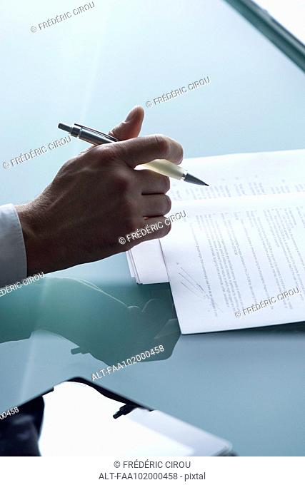 Businessman reviewing document, cropped