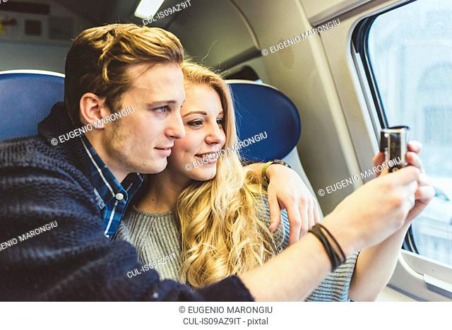 Young couple photographing through train carriage window, Italy