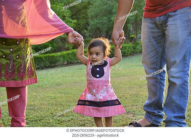 Baby girl trying to walk holding parent's hands, Pune, Maharashtra