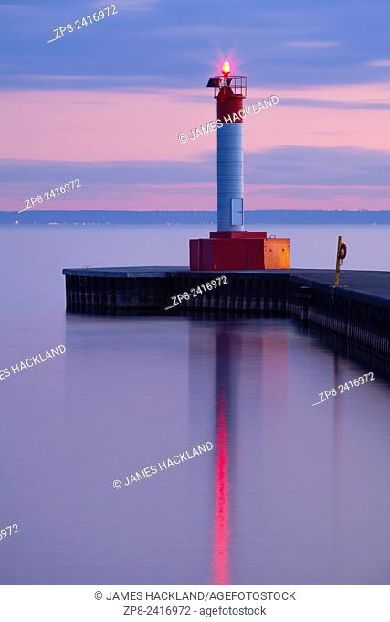 A lighthouse during a colourful sunset on Lake Ontario at Waterworks Park in Oakville, Ontario, Canada