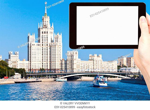 travel concept - tourist photograph Moscow cityscape with Stalin's high-rise building on kotelnicheskaya embankment on tablet pc with cut out screen with blank...