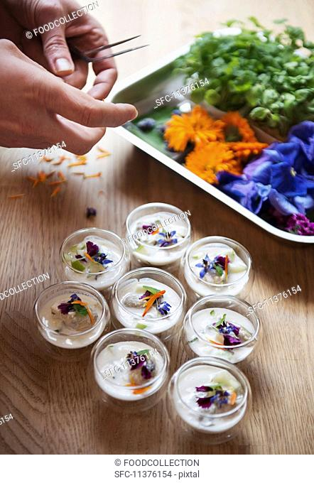 Poached oysters in coconut milk garnished with edible flowers