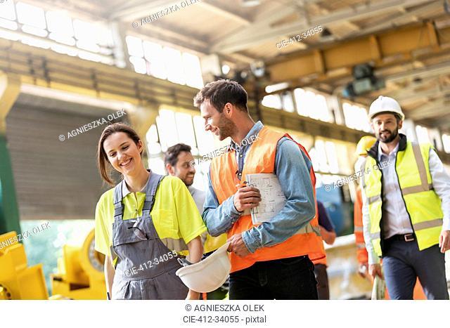Steel workers walking and talking in factory
