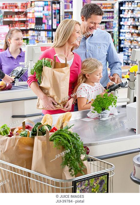 Family Paying For Shopping At Supermarket Checkout