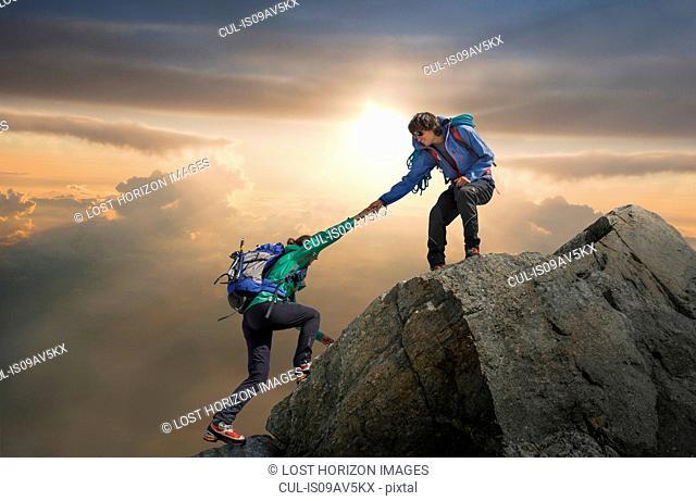 Climber helping partner reach mountain top, Mont Blanc, France
