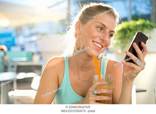 Blond young woman at outdoor cafe looking at her smartphone