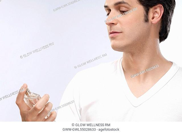 Man looking at a perfume bottle