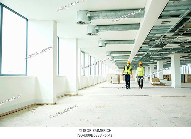 Two workers wearing hi vis vests, walking through newly constructed office space