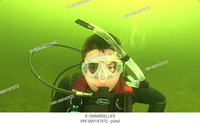 Close up of teenage male scuba diver with air bubbles and goggles