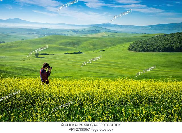 Orcia Valley, Siena district, Tuscany, Italy, Europe. Man takes pictures in a rapessed expanse