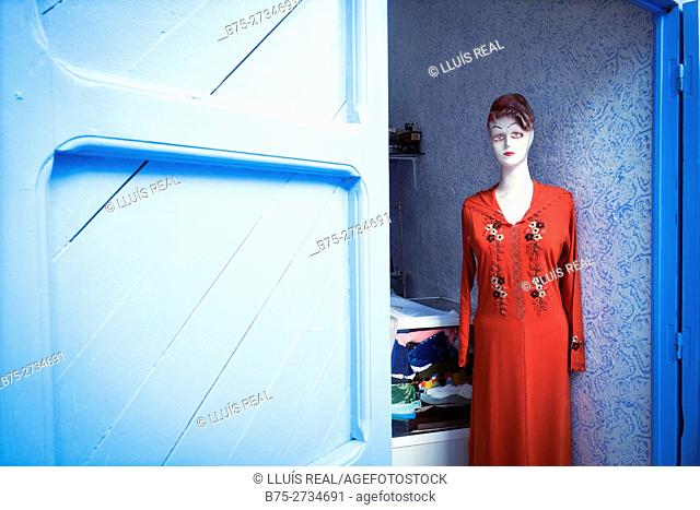 Maniqui at the door of a fashion shop with a red dress. Chaouen, Morocco