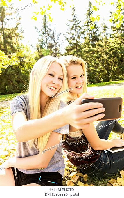 Two sisters having fun outdoors in a city park in autumn and taking a selfie; Edmonton, Alberta, Canada