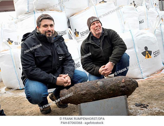 Rene Bennert, firefighter from the bomb disposal team of the Darmstadt regional council (l), and diver Thomas Mueller (r) squatting behind an aerial bomb from...