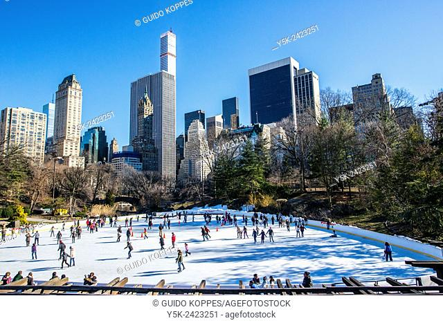New York, USA. View on the Ice Rink in Central Park, Manhattan, with 5th Avenue & 59th Street skyscrapers in the background