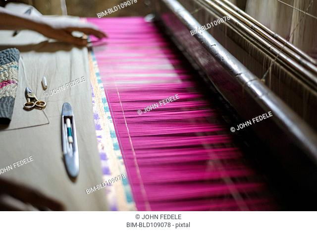 Hand feeling threads in loom