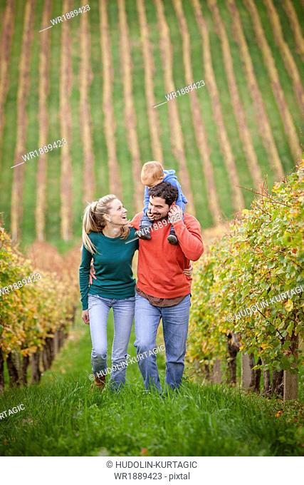 Family with one child walking in a vineyard, Osijek, Croatia