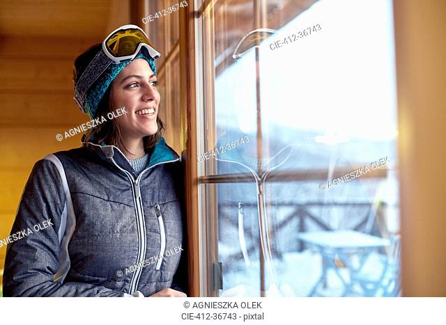 Smiling female skier looking out cabin window