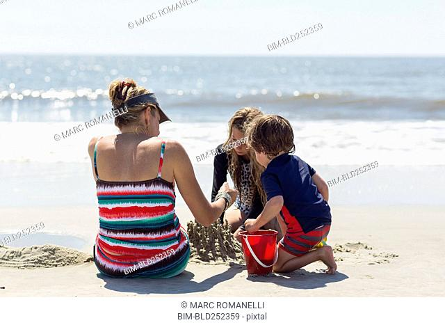 Caucasian family building sand castle at beach