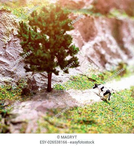 Miniature plastic toy cow on the lawn. Macro photography, shallow DOF
