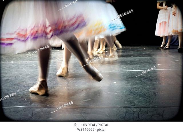 close-up of several feet of classical ballet dancers dancing on a stage in a theater