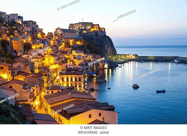 Picturesque coastal town at dusk, with illuminated castle on cliff