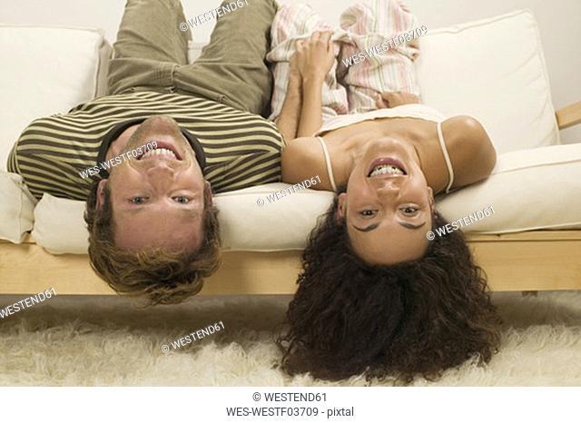 Young couple lying headfirst on sofa