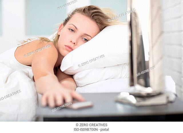 Young woman in bed, reaching for smartphone on bedside table