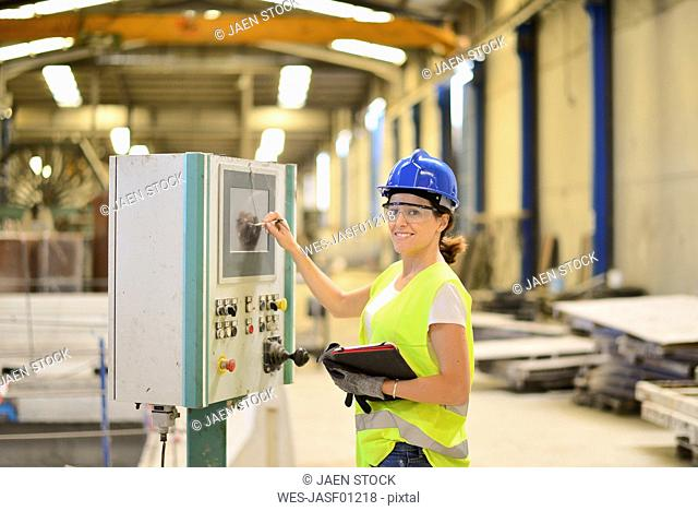 Smiling woman operating control in factory