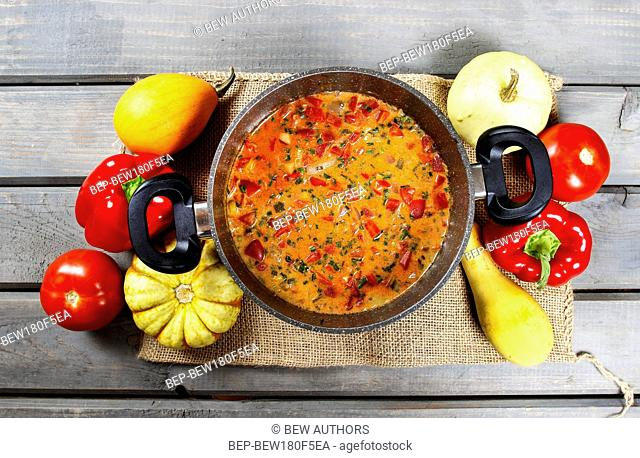 Top view on pot of tomato soup on old wooden table