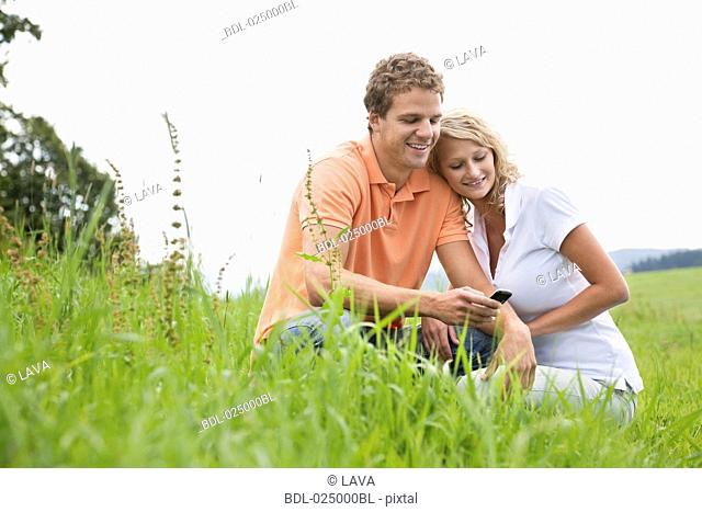 young couple sitting in meeting looking at display of mobile phone