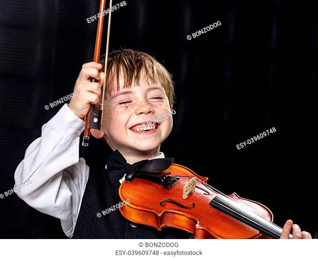 Freckled red-hair boy playing violin. Young musician