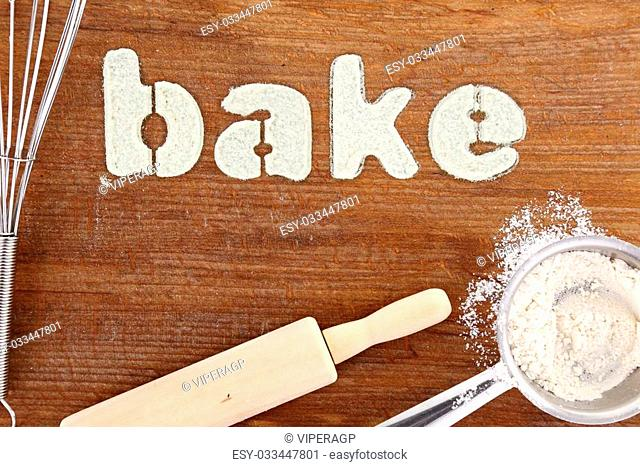 "Stencil word """"bake"""" made with flour on wooden table"