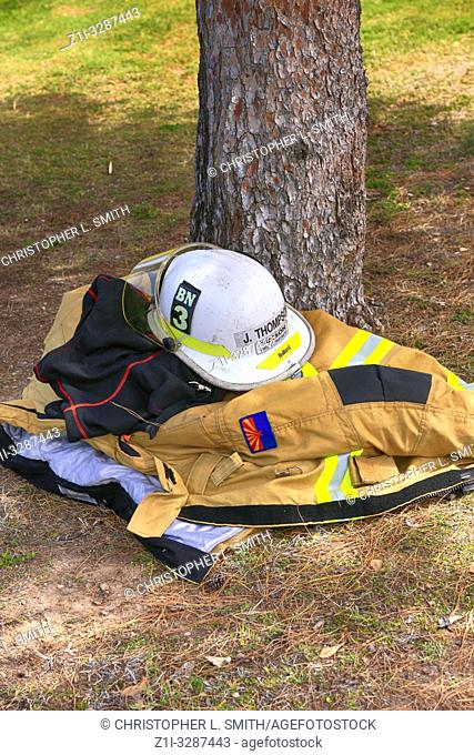 Fireman's heavy jacket and chief's white helmet of the Tucson Fire Dept laying in the shade under a tree away from the Arizona heat