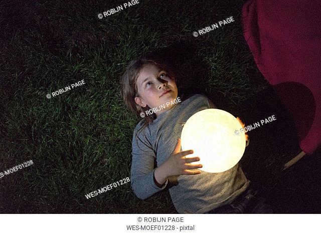 Girl lying on meadow, holding moon