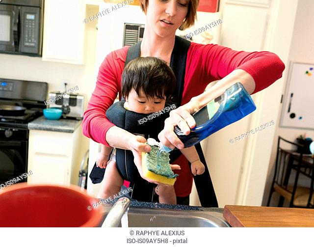 Mother with baby in carrier, washing dishes