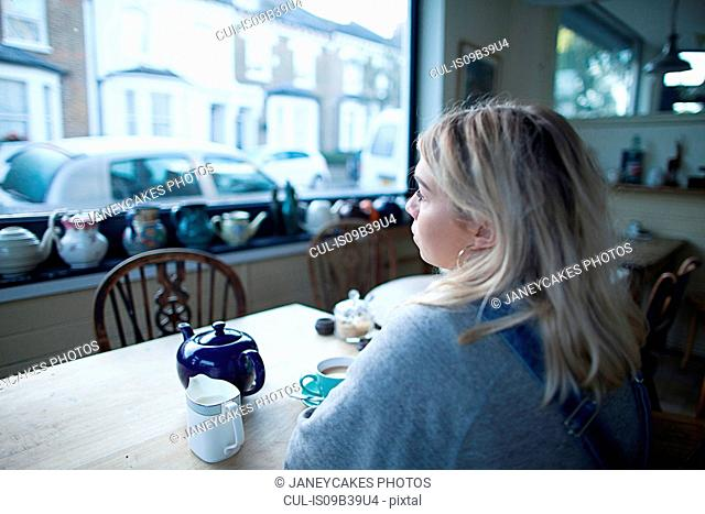 Young woman sitting in cafe, cup of tea and teapot on table, looking out of window