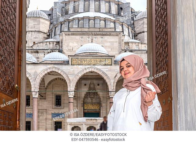 Beautiful Muslim woman in headscarf and fashionable modern trendy clothes poses at gate of Suleymaniye Mosque in Istanbul,Turkey