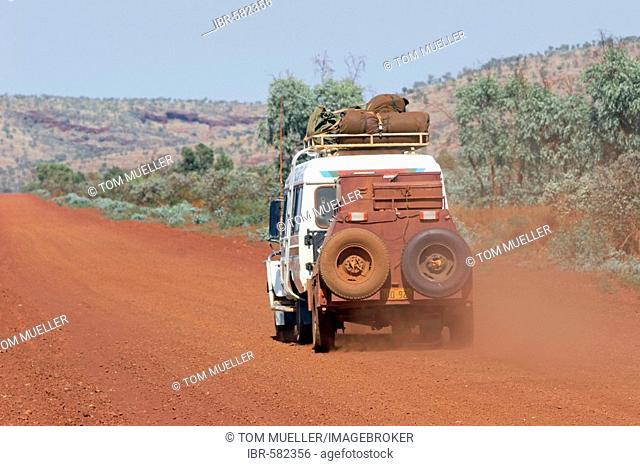 Toyota Landcruiser FJ 75 Arkana safari car driving on road from behind in Karijini National Park Pilbara region western australia WA