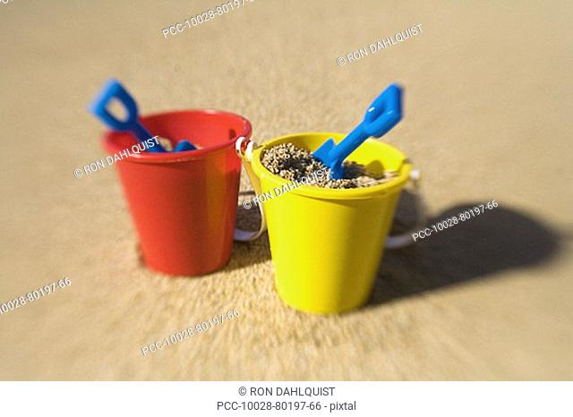 Two sets of brightly colored shovel and pails on a sandy beach