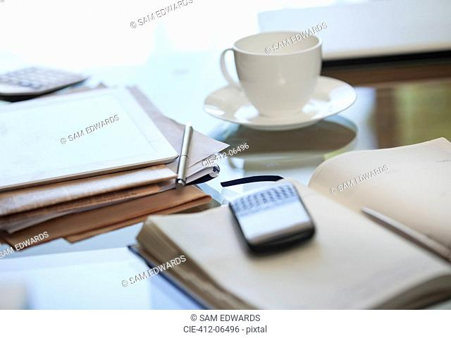 Notebook, cell phone and cup of coffee on desk